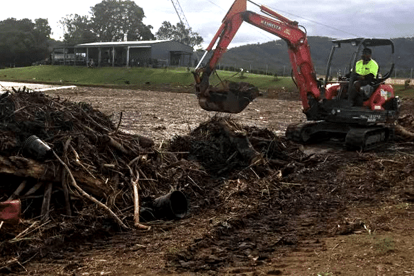 Mini Excavator cleaning up the site